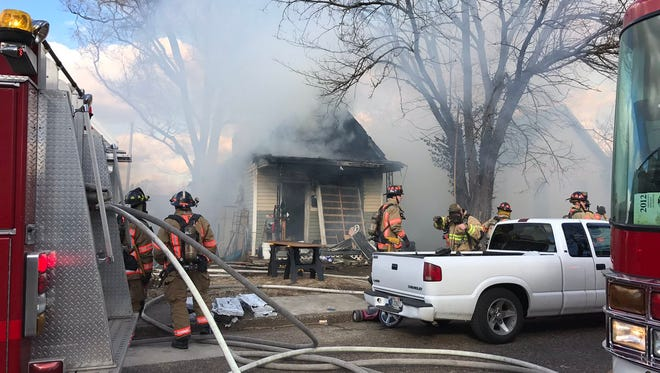 Firefighters battle at a blaze at house on East Sycamore Street on Thursday.
