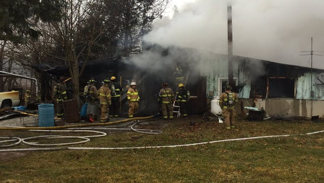 Fire fighters work to extinguish a residential fire in Butler Township on Friday, Jan. 20. Homeowner Dan Wright, who lived in the house for 35 years, believe the fire was caused by a candle left burning overnight.