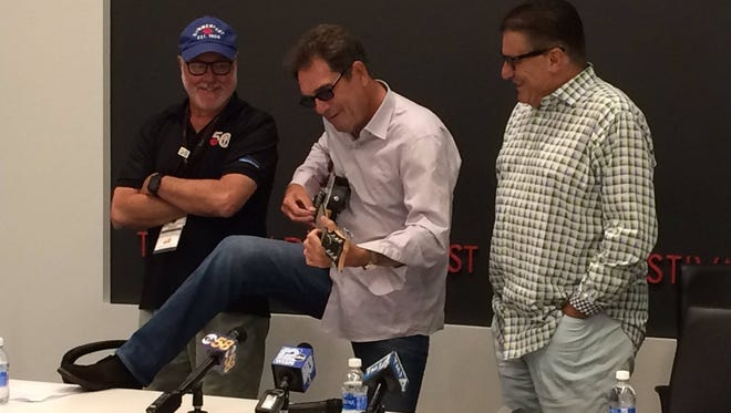 Huey Lewis (center) strums a Summerfest 50th guitar during a Friday afternoon press conference.