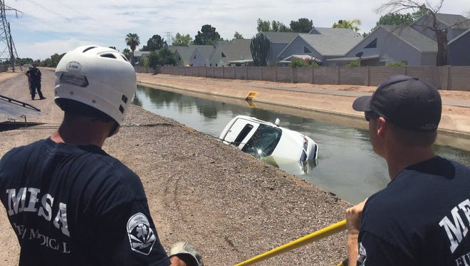 Mesa fire officials pull a car from a canal Monday morning.