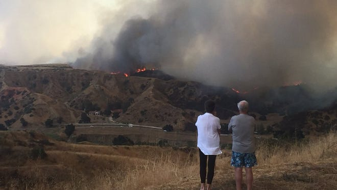 People in Redlands look at the Palmer fire as it began to spread on Saturday.