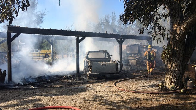 Ventura County fire crews work on a vehicle and carport fire Friday in Somis.