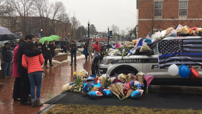 Mourners gather and leave flowers on a police cruiser parked in front of City Hall in Westerville, Ohio, on Sunday, Feb. 11, 2018. Westerville police officers Anthony Morelli and Eric Joering were killed in the line of duty Saturday when a suspect opened fire on them as they responded to a call at a residence.
