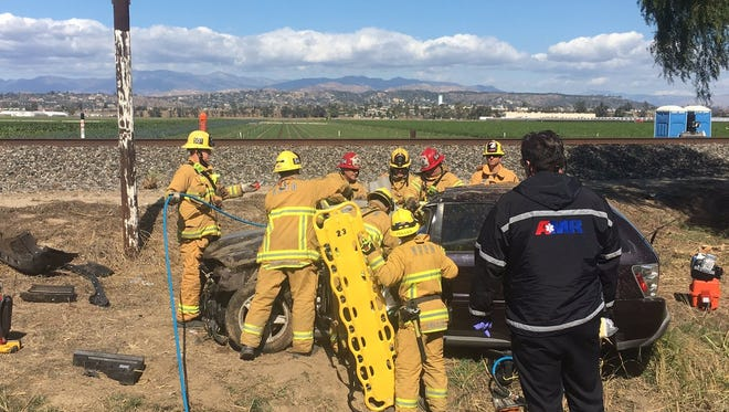 Ventura County fire crews work to extricate a patient from a vehicle Thursday after a rollover crash near the Camarillo Airport.
