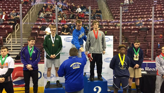 Northern Lebanon's Blaise Bressler accepts his 160-pound gold medal from coach Rusty Wallace during the final day of the District 3 Wrestling Championships at Giant Center on Saturday.