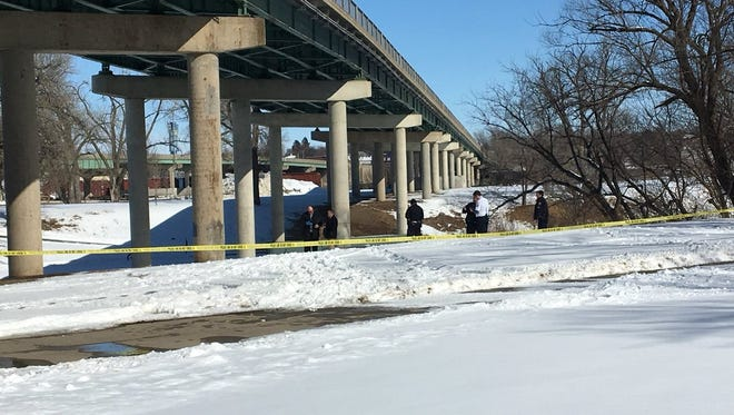 Detectives look through the snow at Falls Park in downtown Sioux Falls.