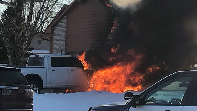 A vehicle fire damages a home in eastern Sioux Falls on Friday.