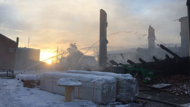 The sun rises as firefighters work to root out hot-spots at a fire that ravaged the Weaver Organ and Piano building in York.