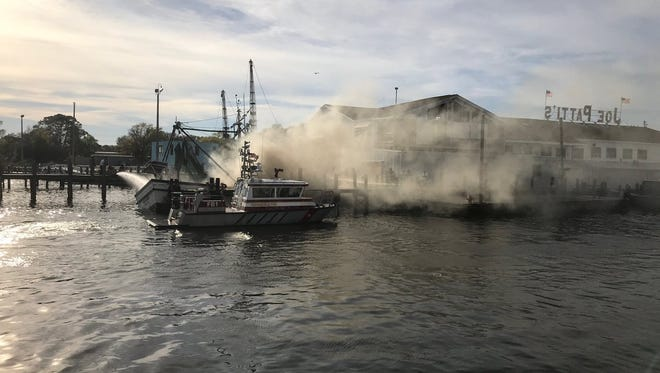 Crews work to extinguish boat fire at Joe Patti seafood in Pensacola on Friday, March 23, 2018.