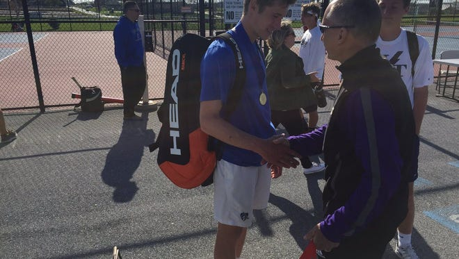 Cedar Crest's Jack Muraika receives his medal from tournament chairman Steve Sweigart after capturing his second straight Lancaster-Lebanon League 3A singles title on Monday.