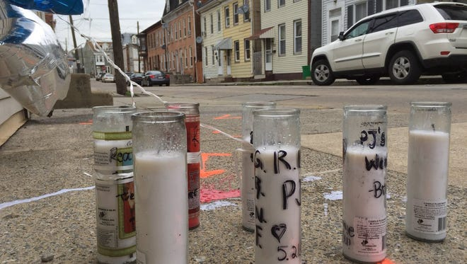 Candles and balloons from friends and family, along with evidence-marking spray-paint, indicate the area on North Franklin Street where 20-year-old Philip Trent Banks, Jr. was shot dead.