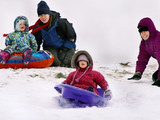 Moms and their kids take on the Nashotah Park sledding hill during a previous winter.