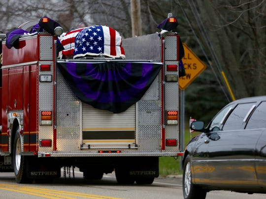 The casket carrying the body of firefighter Patrick Wolterman is carried to Spring Grove Cemetery.