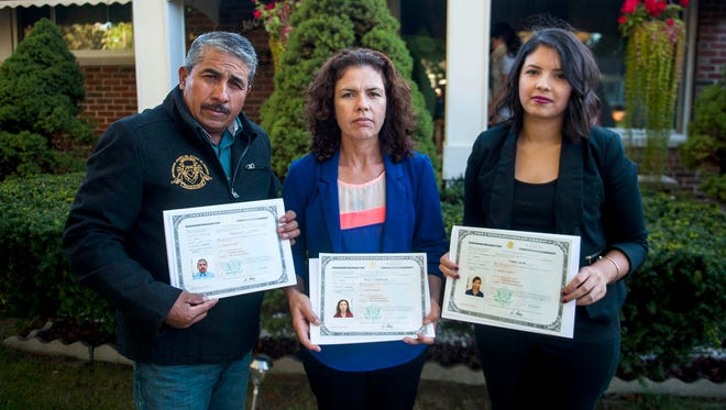 Florencio Jurado poses with his wife, Maria, and daughter, Estefania outside of their home in Detroit on Oct. 8, 2016. All became naturalized in part to participate in the up coming presidential election.