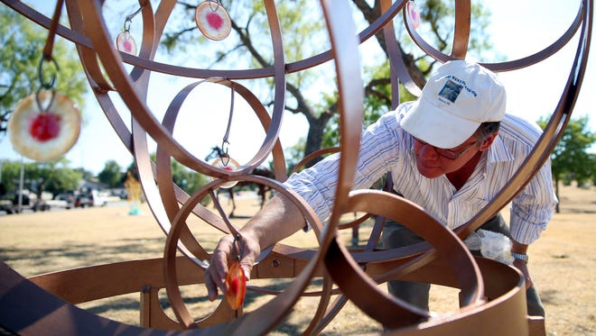 """Artist Peter Mangan, who was part of the Salmon Sculpture Competition in 2015, puts the final touches on his sculpture titled """"New World"""" in Sunken Garden Park."""