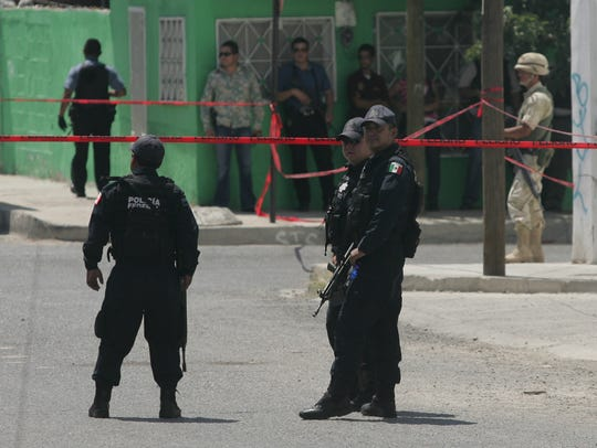Mexican federal police stand guard at a crime scene