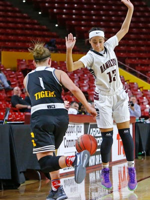 Gilbert's Haley Cavinder tries to bounce the gal off Hamilton's Payton Whitmore as she goes out of bounds during the first half of  their Division I quarterfinal game at Wells Fargo Arena Tuesday, Feb. 23,  2016 in Tempe, Ariz