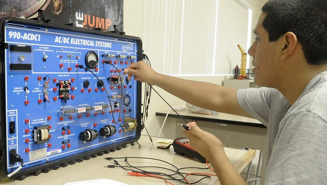 Silver Stage High School senior Gil Pulgarin works on a circuit board in an applied industrial technology class.