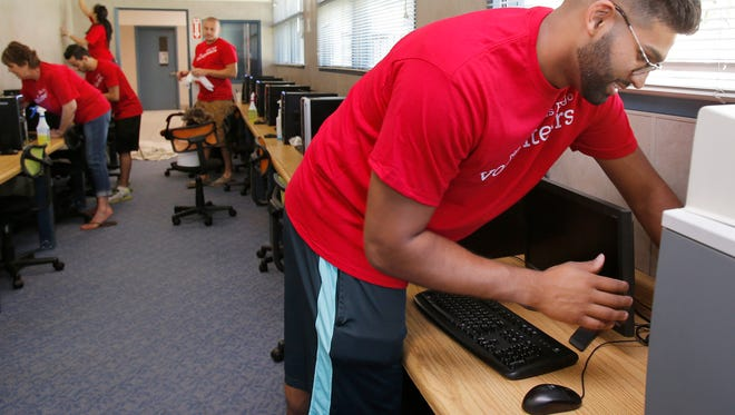 Dillan Weerasinghe, of West Hills, and other employees from Wells Fargo, work on cleaning and painting one of the computer areas at the Boys & Girls Club in Simi Valley as part of the United Way's Day of Caring.