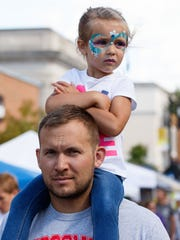 Maggie Plohocky, 3, of Mukwonago gets a ride from her dad, Marty, as they enjoy the Oconomowoc Fall Festival on Sept. 10.