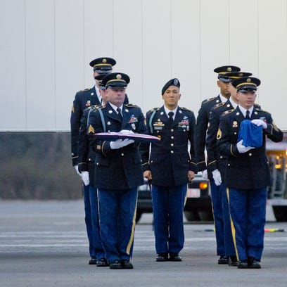 A New York State Honor Guard team prepares to carry