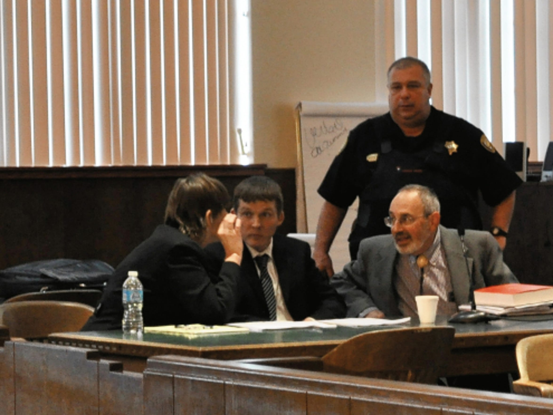 Robert Earley (center), 33, consults with his defense