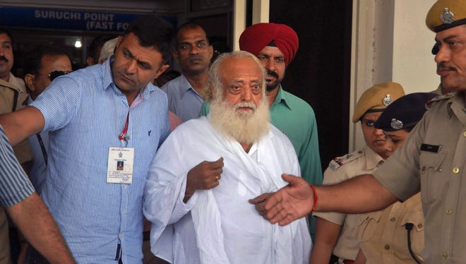 Spiritual guru Asaram Bapu, center, is brought for interrogation by police at India's Jodhpur airport Sept. 1 after being arrested on a rape charge.