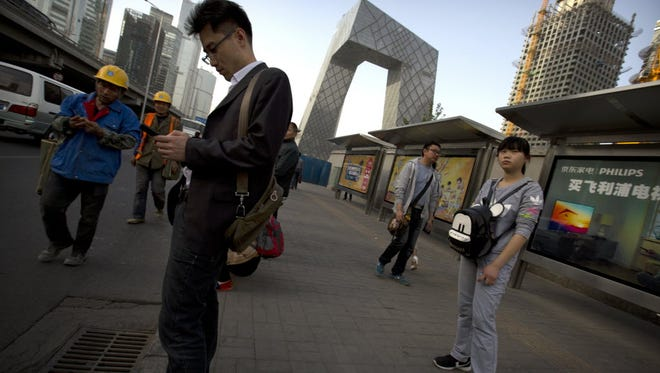 People wait for a bus at a stop near a construction site in central Beijing on April 21.