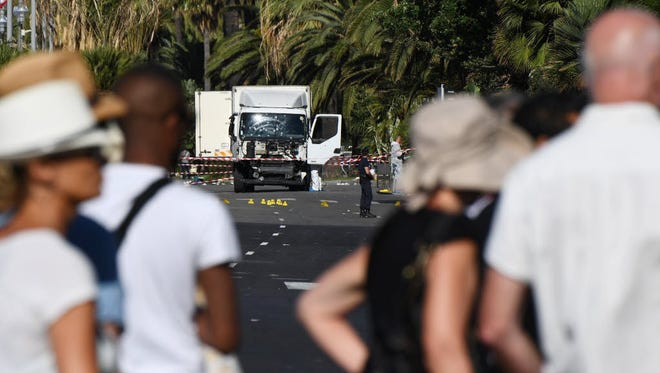 People look at a truck stand guarded by the police on the Promenade des Anglais seafront in the French Riviera town of Nice on July 15.