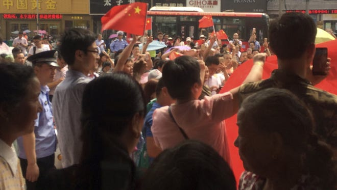 People carrying Chinese flags hold a protest outside a KFC restaurant outlet in Baoying county in east China's Jiangsu province.