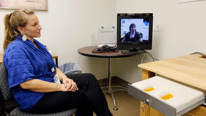 Fiona Tubmen-Scovack, left, clinic manager for Planned Parenthood in Des Moines, watches as Dr. Jill Meadows, Planned Parenthood medical director (on monitor) demonstrates use of the clinic's telemedicine system. The system is used for dispensing abortion pills to patients in outlying clinics.