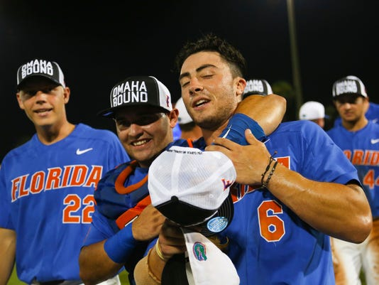 Florida players JJ Schwarz, from left, Mike Rivera and Jonathan India celebrate after defeating Wake Forest 3-0 in an NCAA college super regional baseball game, Monday, June 12, 2017, in Gainesville, Fla. (AP Photo/Matt Stamey)