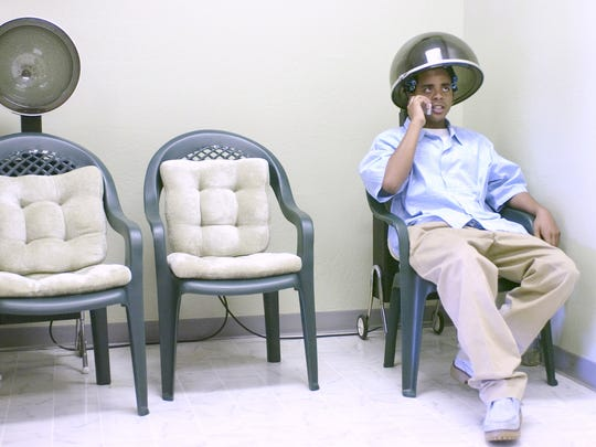 Phoenix City Council candidate Jarrett Maupin, 18, takes a business call while under the dryer at Stylin Katt's Hair Salon in Glendale on July 27, 2005. Maupin's godmother, cosmetologist Veneta Easte, sets his hair twice a week.