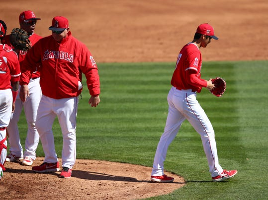 Los Angeles Angels pitcher Shohei Ohtani, right, walks off the mound after being relieved by manager Mike Scioscia, second from right, in the second inning of a spring training baseball game against the Milwaukee Brewers on Saturday, Feb. 24, 2018, in Tempe, Ariz. (AP Photo/Ben Margot)