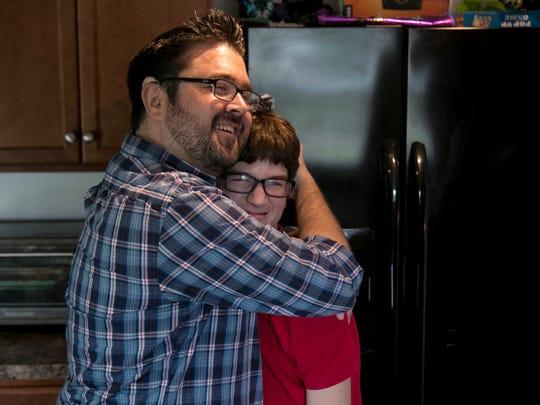 Mike Kain jokes with his oldest son Rowan, 13, on Friday at their Lehigh Acres home.