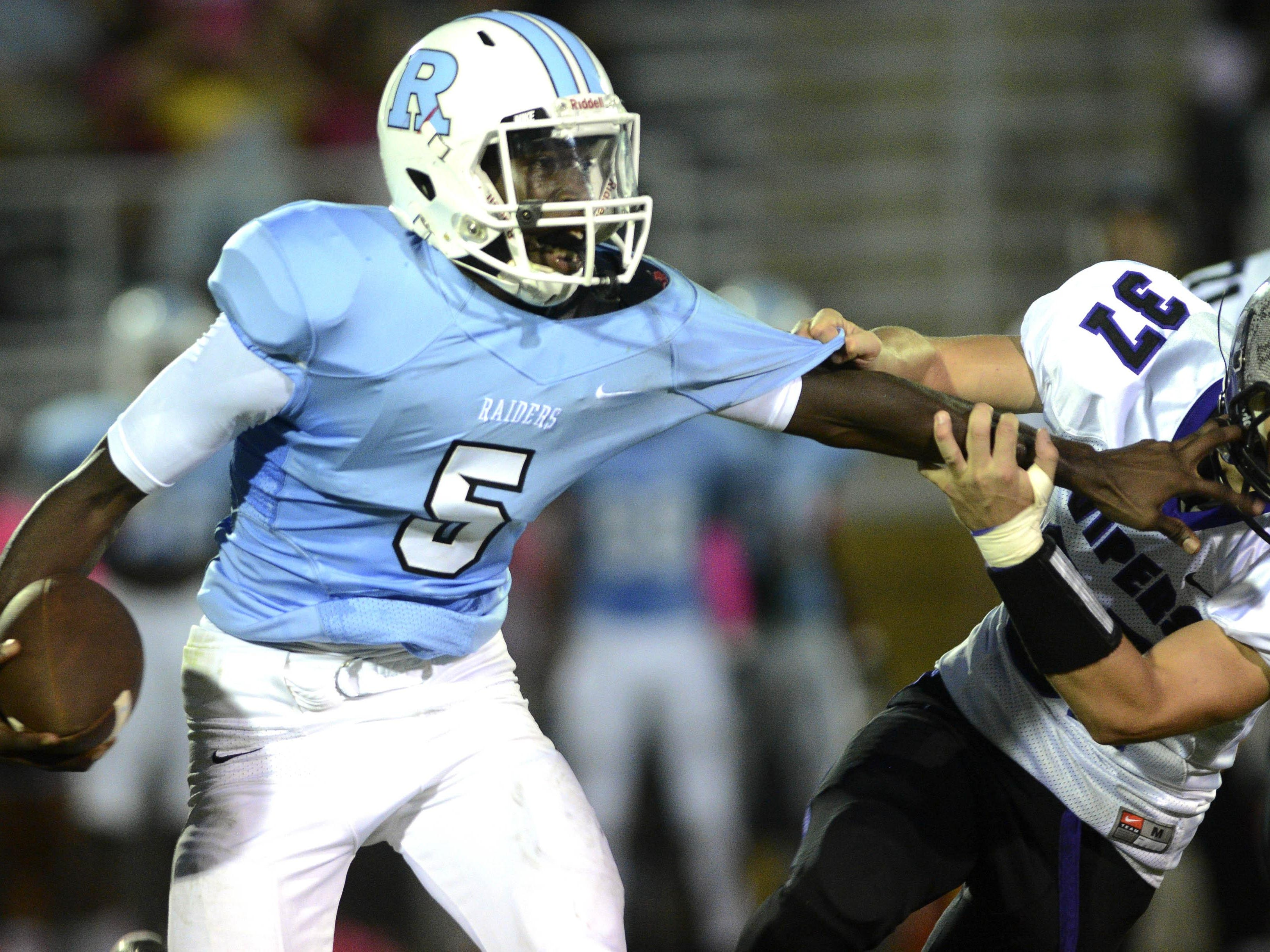 Rockledge QB Jaquez Lyons tries to fend off the tackle of Space Coast player Jared Spinner (37) during Friday's game at McLarty Stadium.