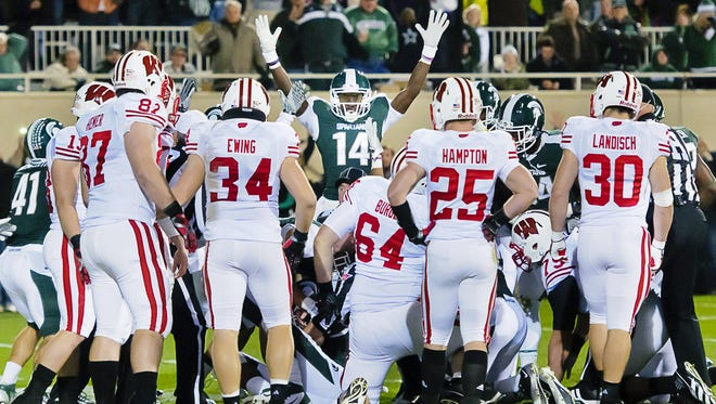 Former Spartan Tony Lippett (14) signals a touchdown as members of the Wisconsin football team look on after MSU blocked a punt and recovered it in the Wisconsin end zone in their last game at Spartan Stadium, on Oct. 22, 2011. Back then Wisconsin's program was still something for MSU to aspire to.