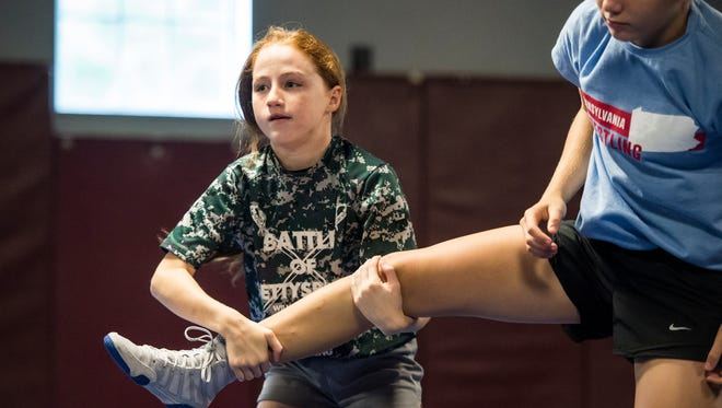 Maddi Wellen, left, wrestles with Montana DeLawder at the Gladiator Wrestling Club in Orrtanna. Wellen, a seventh grader at Bermudian Springs Middle School, competed at the AAU Junior Olympics in Michigan last month where she earned All-American status and won a gold medal in the female division at 65 to 75 pounds.