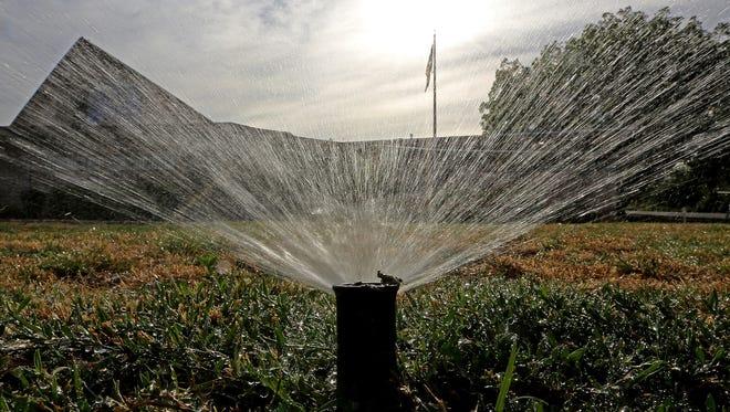 Sprinklers water a lawn.