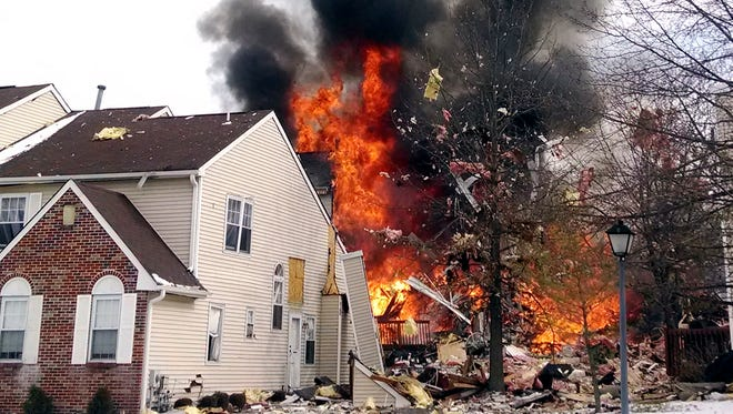 Flames and smoke shoot up after an explosion at a townhouse complex Tuesday, March 4, 2014, in Ewing, N.J.