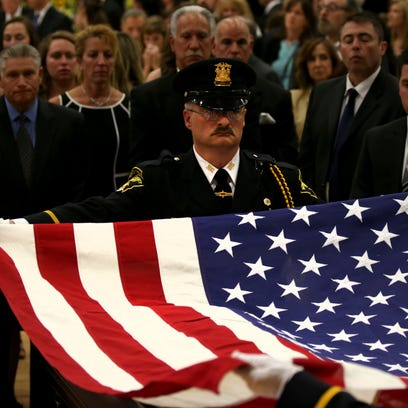 The flag is draped over the casket of  Sheriff Meloni.