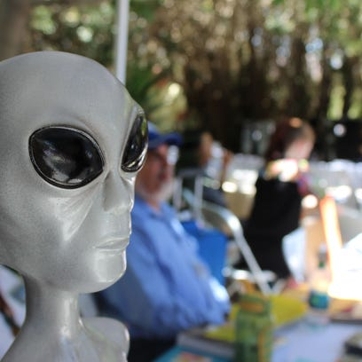 An alien figurine stands stoic as Contact in the Desert