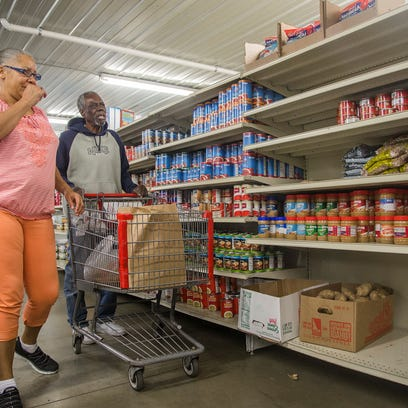 Mona Gatewood of Des Moines, left, walks with food