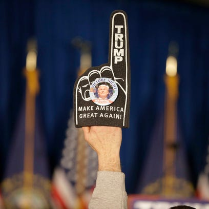 A supporter holds a foam finger sign promoting Donald
