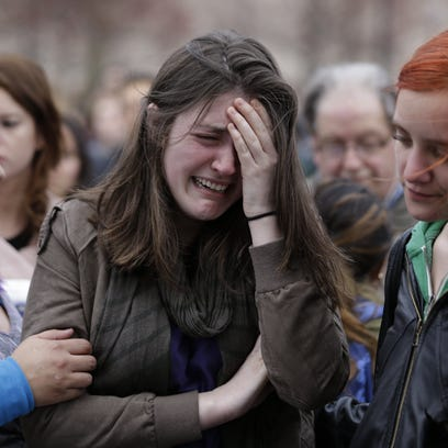 Emma MacDonald, 21, center, cries during a vigil for