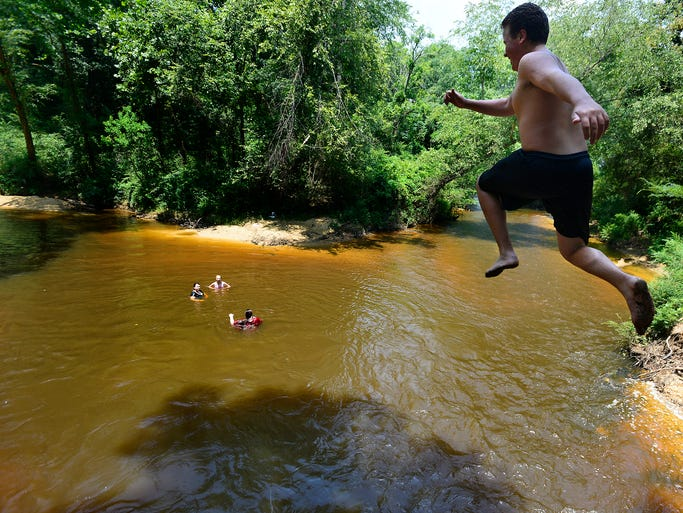 Bradley Sanders leaps into Autauga Creek in Prattville, Ala. while cooling off in the water with friends on Wednesday June 18, 2014.