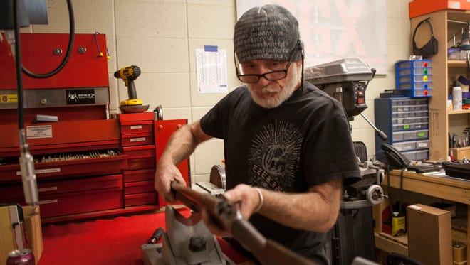 A gun tech at Dixie Gun Worx repairs an old shotgun Tuesday, Jan. 5, 2016.