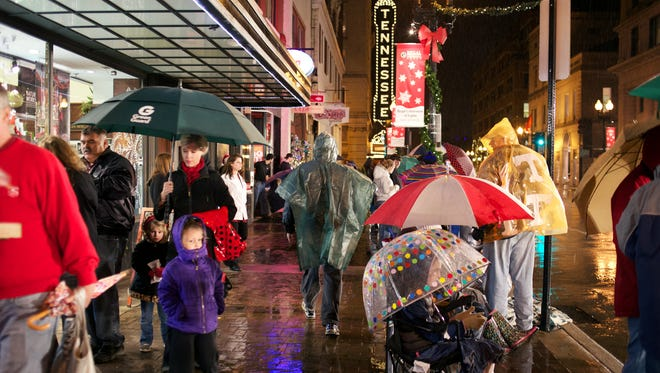 Pedestrians are seen walking in the rain along Gay Street before the WIVK Christmas Parade in Knoxville, Tenn. on Friday, December 6, 2013.  (Shawn Millsaps/Special to the News Sentinel)