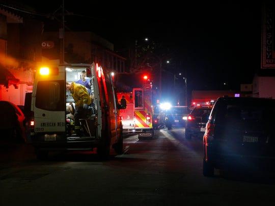 Paramedics speak with a man inside an ambulance after