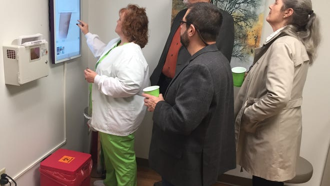 Nurse Lisa Gantt shows off some of the diagnostic aids available at the new Foothills clinic in Easley to Byron Edwards, David Allison and Hilda Anderson.